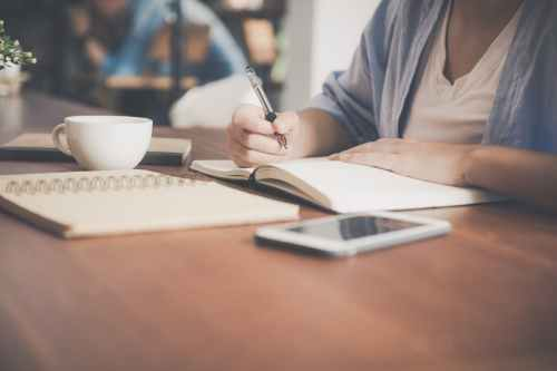 woman writing on a notebook beside teacup and tablet computer